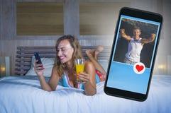 Młoda atrakcyjna i piękna kobieta w łóżkowym używa internecie ogólnospołeczny medialny datuje app na telefonu komórkowego uśmiech zdjęcia stock