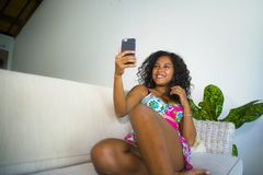 Młoda atrakcyjna i piękna szczęśliwa czarna latyno-amerykański kobieta bierze selfie portreta obrazek z telefonem komórkowym przy fotografia stock