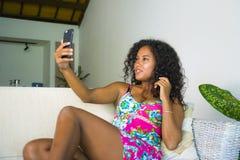 Młoda atrakcyjna i piękna szczęśliwa czarna latyno-amerykański kobieta bierze selfie portreta obrazek z telefonem komórkowym przy obraz stock
