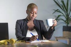 Młoda atrakcyjna i pomyślna czarna afro amerykańska kobieta w biznesowy kurtki pracować poważny przy biurowym laptopem bierze not fotografia stock