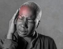 Młoda atrakcyjna i smutna czarna afro Amerykańska kobieta z palcami na ona kierownicza tempa cierpienia migrena i migreny uczucie Fotografia Stock