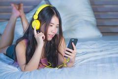 Młoda atrakcyjna i szczęśliwa Azjatycka Chińska kobieta słucha muzyka w telefonie komórkowym na łóżku w domu uśmiecha się brzęcze Fotografia Stock