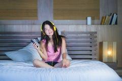 Młoda atrakcyjna i szczęśliwa Azjatycka Chińska kobieta słucha muzyka w telefonie komórkowym na łóżku w domu uśmiecha się brzęcze Zdjęcia Royalty Free