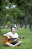 Młoda atrakcyjna kobieta bawić się gitarę akustyczną Fotografia Stock