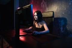 Młoda atrakcyjna kobieta bawić się wideo gry na jej komputerowej jest ubranym hazard słuchawki zdjęcia royalty free