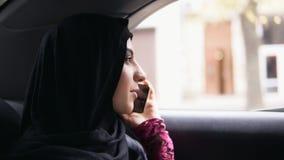 Młoda atrakcyjna kobieta jest ubranym hijab obsiadanie na tylnym siedzeniu w taxi i opowiada na telefonie Slowmotion strzał zdjęcie wideo