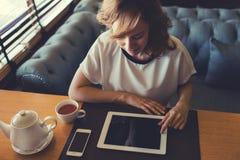 Młoda atrakcyjna kobieta koncentrował czytelniczą elektroniczną książkę na jej cyfrowej pastylce Obrazy Royalty Free