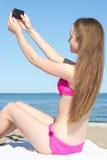 Młoda atrakcyjna kobieta ono fotografuje z telefonem komórkowym o Fotografia Stock