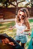 Młoda atrakcyjna kobieta ono uśmiecha się i gotuje przy grilla grilla przyjęciem Przyjaciele, ludzie styl życia pojęcia fotografia stock