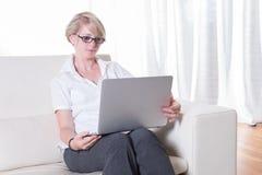 Młoda atrakcyjna kobieta pracuje z laptopem na leżance Fotografia Royalty Free