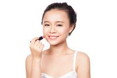 Młoda atrakcyjna kobieta stosuje pomadkę na jej twarzy i patrzeje kamerę, odizolowywającą na bielu Zdjęcia Royalty Free