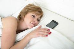 Młoda atrakcyjna kobieta w łóżkowym z telefonem komórkowym jako sypialny partner w internecie i mądrze telefonu nałogu pojęciu sa Fotografia Stock