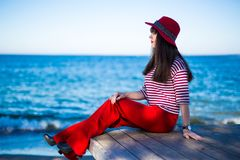 Młoda atrakcyjna kobieta w czerwonym obsiadaniu nad błękitnym niebem i morzem zdjęcia stock