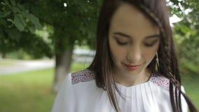 Młoda atrakcyjna kobieta z ładnym uśmiechem chodzi wzdłuż zielonego parka Brunetka jest ubranym hafciarską suknię zbiory