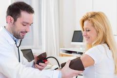 Młoda atrakcyjna lekarka sprawdza pacjenta ciśnienie krwi Obrazy Stock