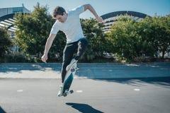 Młoda atrakcyjna mężczyzna jazda i skokowy longboard w parku fotografia royalty free