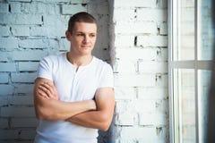 Młoda atrakcyjna mężczyzna pozycja blisko okno i białego ściana z cegieł fotografia stock