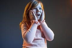 Młoda atrakcyjna nastoletnia dziewczyna patrzeje zaskakujący na zmroku - błękit obraz stock