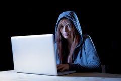 Młoda atrakcyjna nastoletnia kobieta jest ubranym kapiszon na siekać laptopu cyberprzestępstwa cyber przestępstwa pojęcie Fotografia Royalty Free