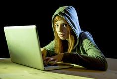 Młoda atrakcyjna nastoletnia kobieta jest ubranym kapiszon na siekać laptopu cyberprzestępstwa cyber przestępstwa pojęcie Obrazy Stock