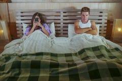 Młoda atrakcyjna para w łóżku z ogólnospołecznymi środkami uzależnia się kobiety używa interneta telefon komórkowego i wzburzoneg obraz royalty free