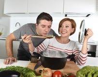 Młoda atrakcyjna pary kuchnia z mężczyzna smacznym jarzynowym gulaszem gotującym jej żony ono uśmiecha się szczęśliwy w domu zdjęcia stock