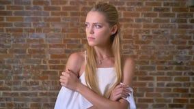 Młoda atrakcyjna smutna blondynki dziewczyna patrzeje kamerę, alarmującą, portret, ściana z cegieł w tle