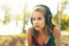 Młoda atrakcyjna sportsmenka słucha muzyka jest ubranym hełmofony Sport, sprawność fizyczna, trening obrazy royalty free
