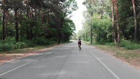 Młoda atrakcyjna triathlete kobieta trenuje na bicyklu w lasowym zadku podąża strzał trutnia widok zbiory