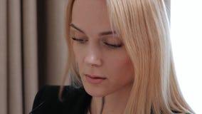 Młoda atrakcyjna w średnim wieku blondynki kobieta w czarnym garniturze i eyeglasses w pokoju hotelowym Pisze wiadomościach dalej zbiory wideo