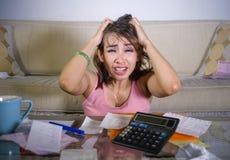 Młoda atrakcyjna zaakcentowana, zmartwiona latynoska kobieta ciągnie i jej kalkulatorskich miesięcznych koszty de i obraz royalty free