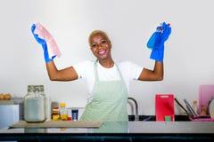 Młoda atrakcyjnego i szczęśliwego czarny afrykanin kobiety cleaning domu amerykańskiego kuchennego mienia kiści detergentowa bute Zdjęcie Stock