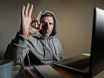 Młoda atrakcyjnego, niebezpiecznego przyglądającego hackera komputerowa fajtłapa pracuje na laptopie i zdjęcie royalty free