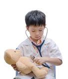 Młoda azjata lekarki chłopiec bawić się niedźwiedź zabawkę i leczy obraz stock