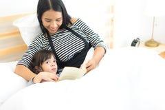 Młoda azjata matka czyta książkę jej córki na łóżkowym nighttime Obraz Stock