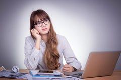 Młoda Azjatycka biurowa kobieta przy nowożytnym biurowym biurkiem, pracuje z laptopem, żadny koncentracja z pracą, odczucia nudzi Zdjęcia Stock