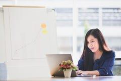 Młoda Azjatycka biznesowa kobieta koncentrował działanie laptop na zakładce obraz stock