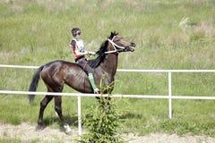 Młoda Azjatycka chłopiec jedzie jej czystego trakenu konia Obraz Royalty Free