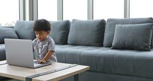 Młoda Azjatycka chłopiec używa notatnika samotnie w domu zbiory