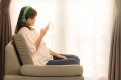 Młoda Azjatycka dziewczyna słucha muzyka z hełmofonem i smarthpho obrazy stock