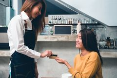 Młoda Azjatycka kobieta robi zapłacie sklep z kawą właściciel kredytową kartą z tłem napoju baru kontuar fotografia stock