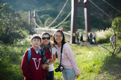 Młoda Azjatycka rodzinna poza obok zawieszenie mosta z backlit zdjęcia stock