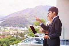 Młoda azjatykcia biznesmen pozycja przy tarasem patrzeje budować Obraz Stock