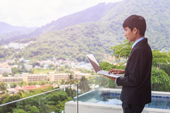 Młoda azjatykcia biznesmen pozycja przy tarasem patrzeje budować Zdjęcia Stock