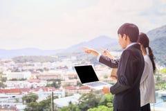 Młoda azjatykcia biznesmen pozycja przy tarasem patrzeje budować Zdjęcie Stock