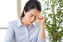 Młoda azjatykcia biznesowa kobieta z migreną obraz royalty free