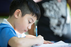 Młoda azjatykcia chłopiec robi jego pracie domowej Fotografia Royalty Free