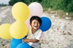 Młoda azjatykcia chłopiec uśmiechnięta i roześmiana podczas gdy trzymający balon obraz stock