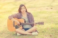 Młoda azjatykcia dziewczyna bawić się gitarę Zdjęcie Royalty Free