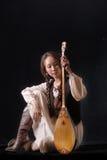 Młoda azjatykcia dziewczyna w obywatel sukni bawić się komuz na czarnym tle Fotografia Stock